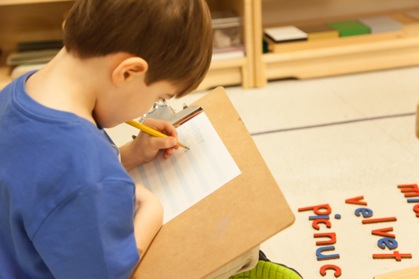 Young boy writing on paper