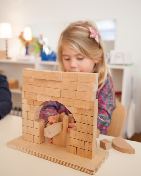 Young girl playing with wooden blocks