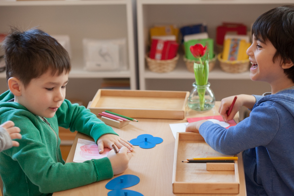 Two young boys drawing pictures