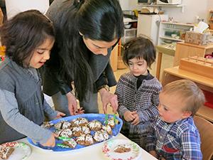 Teacher serving cookies to children
